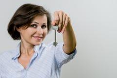 Erwachsene lächelnde Geschäftsfrau oder Immobilienagentur, die Schlüssel f zeigen Stockfotografie