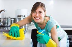 Erwachsene Mädchenabstaubenoberflächen in der Küche Lizenzfreie Stockbilder