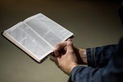 Erwachsene männliche Hände, die ein geöffnetes Buch mit beiden Händen in einer Faust mit einem grauen konkreten Hintergrund halte lizenzfreies stockfoto