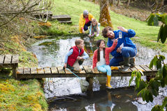 Erwachsene mit Kindern auf Brücke in Tätigkeits-der im Freien Mitte Lizenzfreie Stockbilder