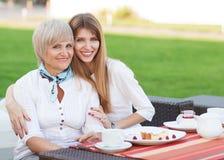 Erwachsene Mutter und trinkender Tee oder Kaffee der Tochter Stockfoto