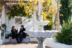 Erwachsene Paare in der Liebe, die in einem Park sitzt lizenzfreies stockbild