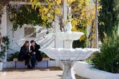 Erwachsene Paare in der Liebe, die in einem Park sitzt lizenzfreie stockfotos