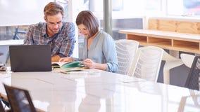 Erwachsene Paare, die an einem Konferenztische zusammenarbeiten Lizenzfreie Stockfotos