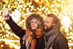 Erwachsene Paare, die selfie in der Stadt während der Weihnachtszeit nehmen lizenzfreie stockfotografie