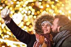 Erwachsene Paare, die selfie in der Stadt während der Weihnachtszeit nehmen stockfoto