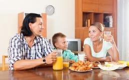 Erwachsene Paare mit dem Jugendlichen, der mit Saft frühstückt Lizenzfreies Stockbild