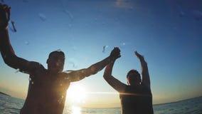 Erwachsene Paarsprünge in das Wasser bei Sonnenuntergang Ein paar machen Mann und Frau einen Sprung in das Wasser, das Unterwasse stock video footage