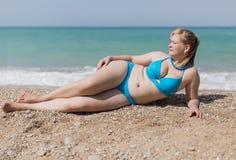 Erwachsene pralle Frau im blauen Bikini, der auf Kiesel liegt Stockbild