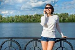Erwachsene schöne lächelnde Frau, die am Telefon spricht Lizenzfreies Stockfoto