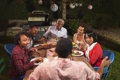 Erwachsene schwarze Familie, die am Abendessen in ihrem Garten spricht lizenzfreies stockbild