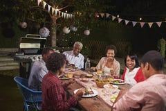 Erwachsene schwarze Familie, die zusammen Abendessen in ihrem Garten genießt stockfotos