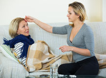 Erwachsene Tochter, die um älterer Mutter mit schlechtem Kamin sich kümmert Stockbild