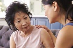 Erwachsene Tochter, die zu Hause mit deprimierter Mutter spricht Stockbild