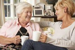 Erwachsene Tochter, welche die ältere Mutter sitzt auf Sofa At Home besucht stockfotografie