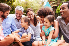 Erwachsene und Kinder, die auf dem Gras in einem Garten sitzen lizenzfreie stockfotos