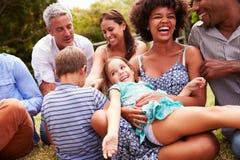 Erwachsene und Kinder, die auf dem Gras in einem Garten sitzen lizenzfreies stockbild
