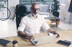 Erwachsener bärtiger Geschäftsmann, der an mobiler Laptop-Computer beim Sitzen am Holztisch arbeitet lizenzfreies stockbild