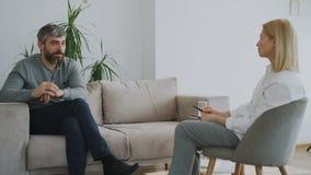 Erwachsener bärtiger Mann, der zuhause über seine Probleme zum Psychologen in ihrem Büro spricht stock footage