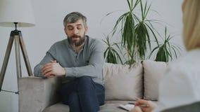 Erwachsener bärtiger Mann, der zuhause über seine Probleme zum Psychologen in ihrem Büro spricht stock video