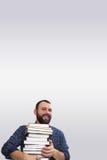 Erwachsener Bartmann des Studenten mit Stapel des Buches in einer Bibliothek lizenzfreies stockbild