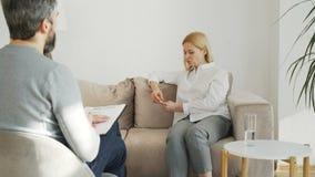 Erwachsener betonte die Frau mit Krise zuhause sprechend mit männlichem Berufspsychoanalytiker im Psychotherapiebüro stock footage