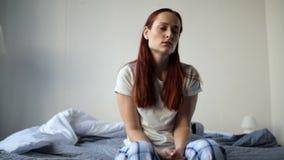 Erwachsener betonte heraus die Frau, die in ihrem Schlafzimmer sitzt stock footage