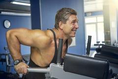 Erwachsener Bodybuilder wird von den Stangen zusammengedrückt Stockfotos