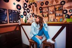 Erwachsener Brunette, der weg Stange betrachtet und Glas mit cockta hält lizenzfreie stockfotografie