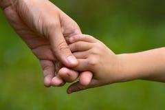 Erwachsener, der eine Kinderhand hält Lizenzfreie Stockbilder