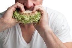 Erwachsener, der voll ein Sandwich von Alfalfasprossen isst Lizenzfreie Stockfotografie