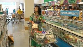 Erwachsener, elegante Frau trägt einen Warenkorb mit Käufen vor stock video footage