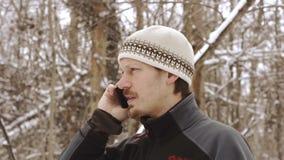 Erwachsener ernster Mann, der draußen am Telefon im Winter spricht stock video