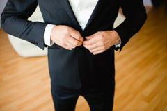 Erwachsener fester Bräutigamknopf seine Klage Stockfoto