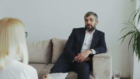 Erwachsener Geschäftsmann, der auf der Couch spricht mit weiblichem Psychotherapeuten im Büro sitzt stock footage