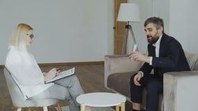 Erwachsener Geschäftsmann, der mit weiblichem Psychotherapeuten und dem Trinkwasser sitzt auf Couch im Psychologebüro spricht stock video footage