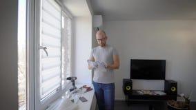 Erwachsener Heimwerker, der am Fenster eine Anweisung Innen liest stock video footage