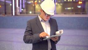 Erwachsener Ingenieur oder Architekt benutzt eine Tablette in Kraft Schreibt eine Mitteilung oder überprüft eine Zeichnung stock footage