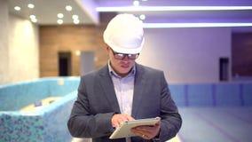 Erwachsener Ingenieur oder Architekt benutzt eine Tablette in Kraft Schreibt eine Mitteilung oder überprüft eine Zeichnung stock video