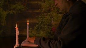Erwachsener kaukasischer Mann, der durch Tabelle nachts und gelesenes Buch mit Paarweißkerzen sitzt stock video footage