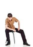 Erwachsener Kerl sitzt auf einem Isolathintergrund Lizenzfreie Stockbilder
