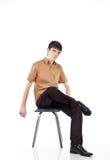 Erwachsener Kerl sitzt auf Isolat backout Lizenzfreies Stockfoto