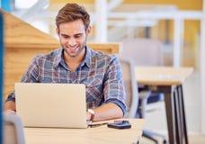 Erwachsener lächelnder Mann, während er an seinem Laptop arbeitet Stockbild