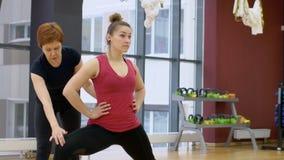 Erwachsener Lehrer hilft einer Frau mit Ausdehnung von den Beinmuskeln, die in der Turnhalle stehen stock video footage
