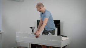 Erwachsener Mann beendet einen Zusammenbau des weißen Schreibtisches, in einem flachen, Öffnung froh in überprüfen und Kamera in  stock video footage