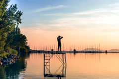 Erwachsener Mann bewundern den Sonnenuntergang auf dem Pier Lizenzfreie Stockfotografie