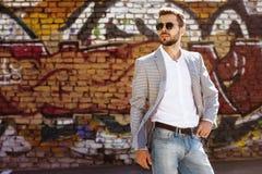 Erwachsener Mann bleibt auf dem graffity Hintergrund lizenzfreie stockfotografie