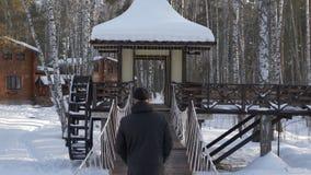 Erwachsener Mann, der auf dekorative Brücke in der Winterstadtpark-Rückseitenansicht geht stock video