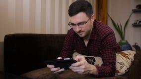 Erwachsener Mann, der auf dem Sofa aufpasst unter Verwendung des Spielens der digitalen Tablette der Spiele sich entspannt stock footage