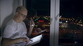 Erwachsener Mann, der auf Fensterbrett- und Grasenbuchseiten mit Taschenlampe in der Dunkelheit sitzt stock footage